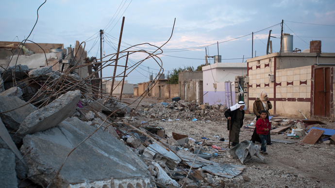 Residents pass by buildings destroyed in a regime's bombardment in Ras al-Ain (AFP Photo / Giulio Petrocco)
