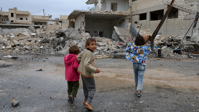 Syrian children walk past buildings destroyed in an air strike by regime forces on the northern Syrian town of Taftanaz, in the Idlib province (AFP Photo / Philippe Desmazes)
