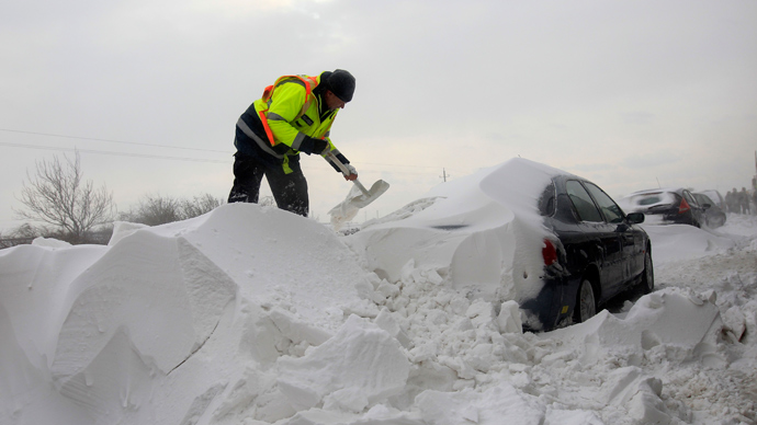 A member of the Hungarian rescue team removes snow from a car at the M1 highway, 80 km west of Budapest, March 15, 2013 (Reuters / Laszlo Balogh)