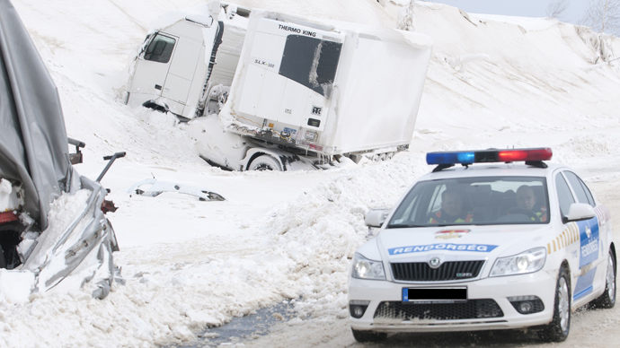 A police car arrives at the site of an accident involving a truck and cars at the E71 motorway, nearby the Croatian, Slovenian and Hungarian borders on March 15, 2013 a day after a heavy snow storm hit the area (AFP Photo / Szilard Gergely)