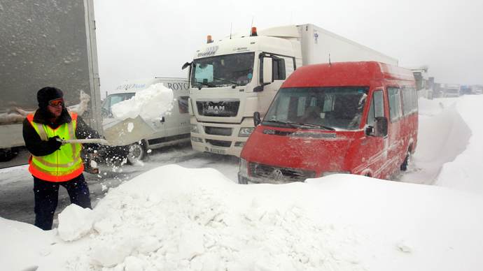 A member of the Hungarian rescue team tries to clear the road at the M1 highway, 80 km west of Budapest, March 15, 2013 (Reuters / Laszlo Balogh)