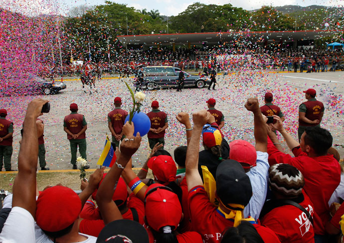 People react as the hearse carrying the body of Venezuela's late President Hugo Chavez drives past during his funeral parade in Caracas March 15, 2013.(Reuters / Tomas Bravo)