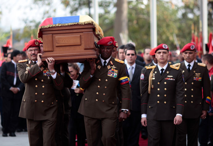 """Handout picture released by the Venezuelan presidency showing members of the presidential Honour Guard carrying the coffin with the remains of late Venezuelan President Hugo Chavez as it arrives at a temporary resting place at the former """"4 de Febrero"""" barracks -- a barracks-turned-museum that the former paratrooper had used as his headquarters during a failed 1992 coup attempt -- in Caracas, on March 15, 2013.(AFP Photo / Presidencia)"""