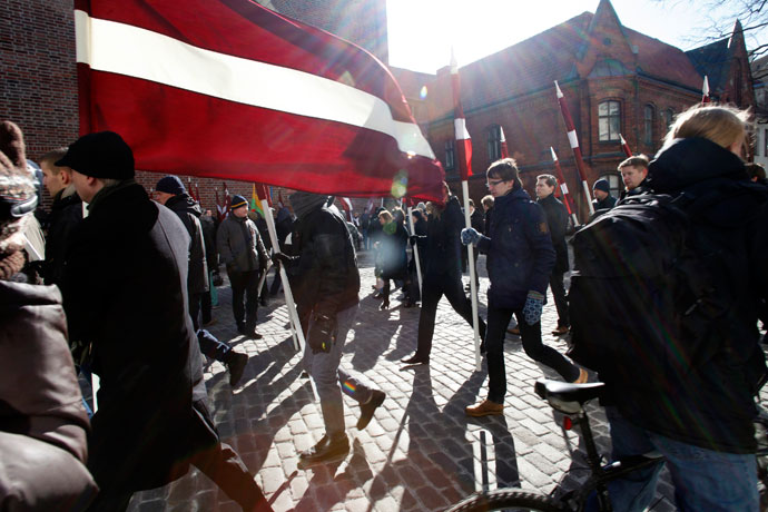 People hold Latvian national flags during the annual procession commemorating the Latvian Waffen-SS (Schutzstaffel) unit, also known as the Legionnaires, in Riga March 16, 2013.(Reuters / Ints Kalnins)