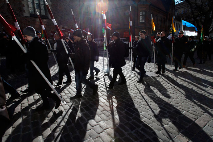 People hold Latvian and Estonian (R) national flags during the annual procession commemorating the Latvian Waffen-SS (Schutzstaffel) unit, also known as the Legionnaires, in Riga March 16, 2013.(Reuters / Ints Kalnins)