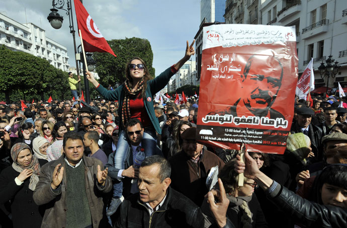 Tunisian people shoot slogans during a demonstration to mark the 40th day of mourning after the death of anti-Islamist opposition leader Chokri Belaid (featured on poster) on March 16, 2013.(AFP Photo / Fethi Belaid)