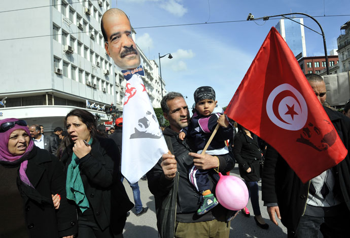 A Tunisian young boy holds a national flag in his father's arms during a demonstration to mark the 40th day of mourning after the death of anti-Islamist opposition leader Chokri Belaid (featured on poster) on March 16, 2013 .(AFP Photo / Fethi Belaid)