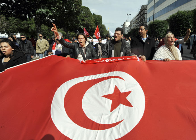 Tunisian people wave a giant national flag during a demonstration to mark the 40th day of mourning after the death of anti-Islamist opposition leader Chokri Belaid (featured on poster) on March 16, 2013.(AFP Photo / Fethi Belaid)