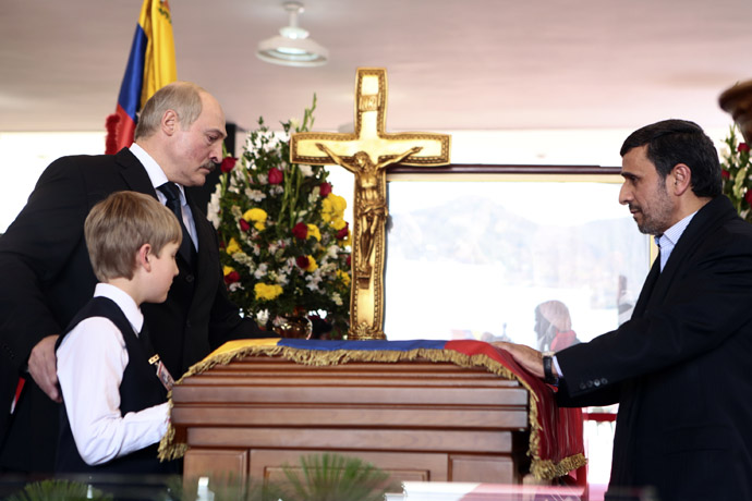 This handout picture released by Venezuelan presidency press office shows Iranian President Mahmoud Ahmadinejad (R), Belarusian President Alexander Lukashenko (L) and his son Nikolai paying their last respects to the coffin of late Venezuelan President Hugo Chavez in Caracas, on March 8, 2013. (AFP Photo/Miguel Angel Angul)