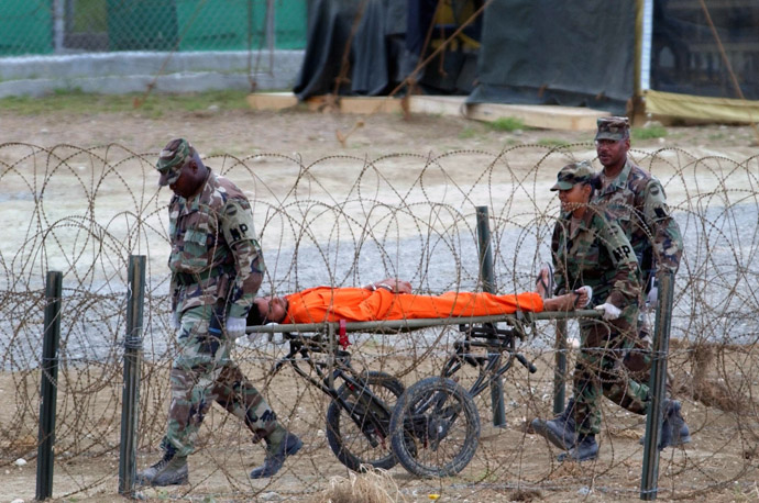 A detainee is carried by military police after being interrogated by officials at Camp X-Ray at the U.S. Naval Base at Guantanamo Bay, Cuba, Wednesday, Feb. 6, 2002. (Reuters)