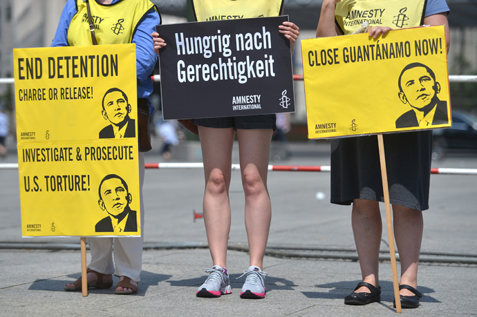 "Activists from Amnesty International human rights association hold posters reading ""End Detention Charge or Release"", ""Close Guantanamo Now"" and displaying a drawing featuring US President Barack Obama during a protest action on the Potsdamer Platz in Berlin, on June 19, 2013 (AFP Photo / Oliver Lang)"