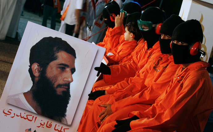 Protesters dressed in orange prison outfits and black masks attend a demonstration outside the US embassy in Kuwait City, calling for the release of Kuwaiti prisoners still behind the bars at the US detention camp in Guantanamo Bay (AFP Photo / Yasser Al-Zayyat)