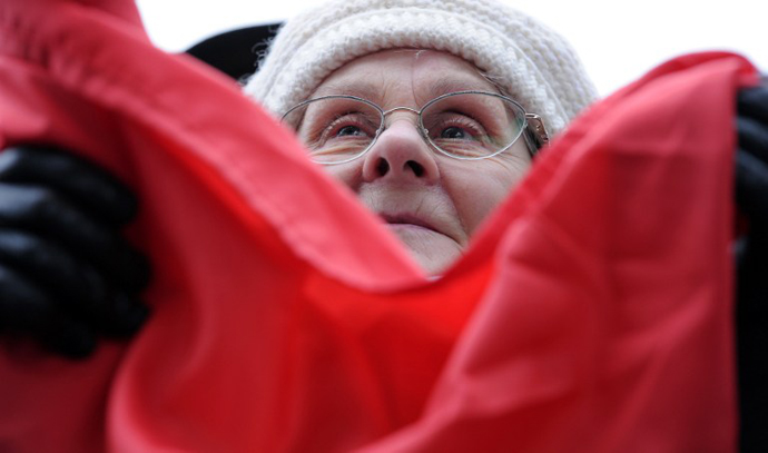An elderly woman holds an Hungarian flag as she takes part in a demonstration on March 17, 2013. (AFP Photo / Attila Kisbenedek)