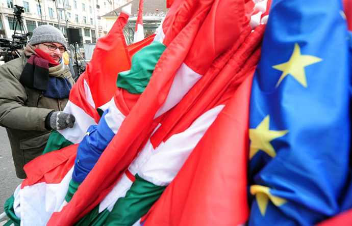 A prepares Hungarian and European flags as he takes part in a demonstration on March 17, 2013. (AFP Photo / Attila Kisbenedek)