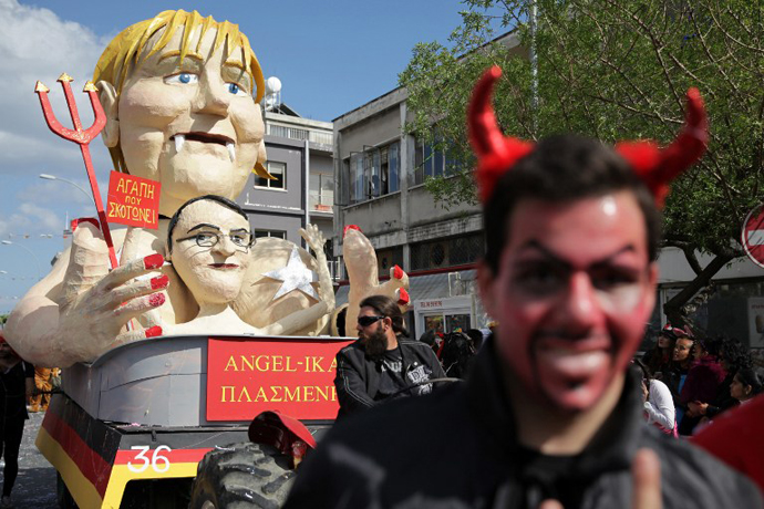 Cypriots walk past a papier-machÈ statue caricaturing German Chancellor Angela Merkel and President of Cyprus Nikos Anastasiadis, in an annual carnival in the southern city of Limassol, March 17, 2013. (AFP Photo / Yiannis Kourtoglou)