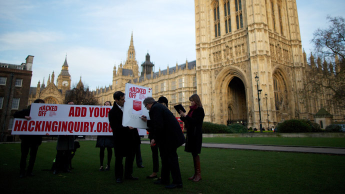 Members of the Hacked Off Campaign stage a photocall to illustrate how many people have signed the petition for a free but accountable press in the United Kingdom out side of Parliament in London on December 3, 2012. (AFP Photo/Andrew Cowie)