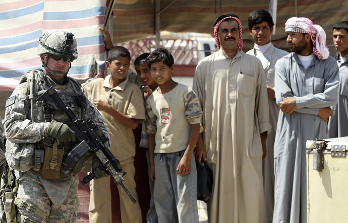 A U.S. soldier stands next to Iraqi residents as he patrols in Mosul, 390 km (240 miles) north of Baghdad September 5, 2010. (Reuters/Saad Shalash)