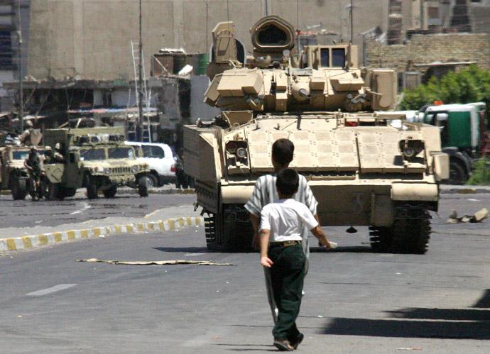 Two Iraqi boys walk near a US tanks as it patrol Baghdad's Sunni neighborhood of Azamiya 01 July 2004. (AFP Photo/Esaam Al-Sudani)