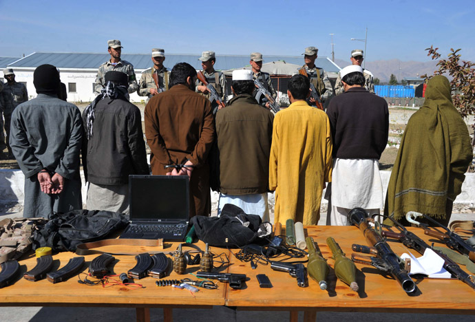 Taliban fighters stand handcuffed near seized weapons as they are displayed to the media at a police headquarters in Jalalabad on March 2, 2013. (AFP Photo/Noorullah Shirzada)