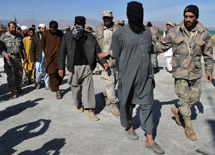 Taliban fighters are led by police as they are displayed to the media at a police headquarters in Jalalabad on March 2, 2013. (AFP Photo/Noorullah Shirzada)
