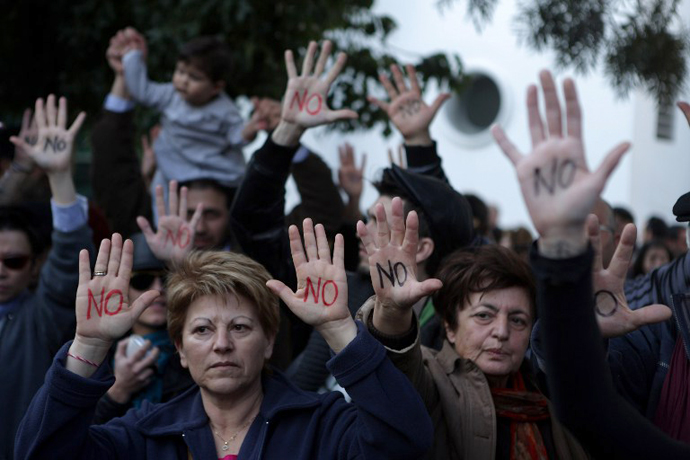"Cypriots show their palms reading ""No"" during a protest against an EU bailout deal outside the parliament in Nicosia on March 18, 2013. (AFP Photo / Patrick Baz)"