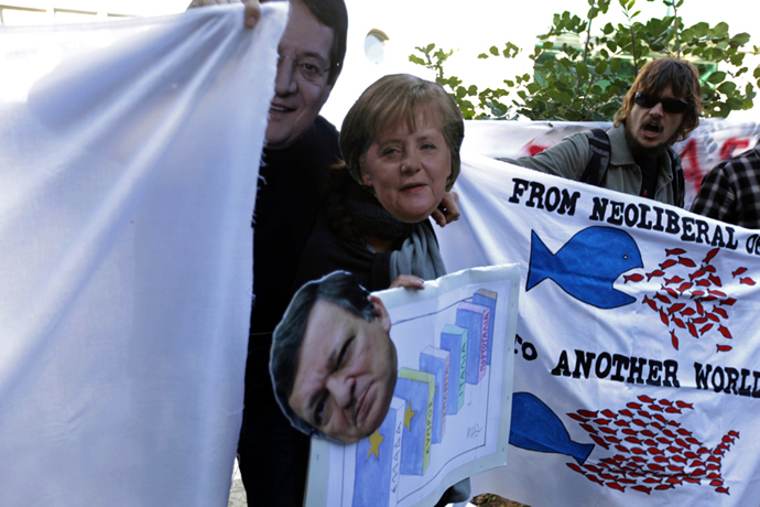 Cypriots holding cut-out masks of German Chancellor Angela Merkel, European Commission head Jose Manuel Barroso and Cypriot President Nicos Anastasiades take part in a protest against an EU bailout deal outside the parliament in Nicosia on March 18, 2013. (AFP Photo / Patrick Baz)