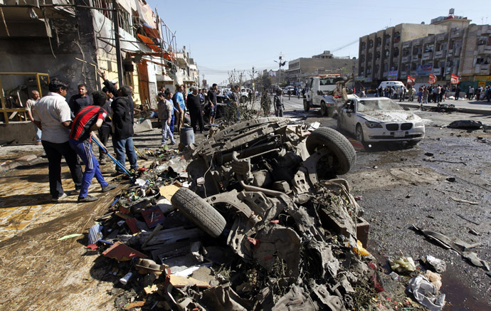 Residents gather at the site of a car bomb attack in the AL-Mashtal district in Baghdad March 19, 2013. (Reuters/Qahtan al-Sudani)