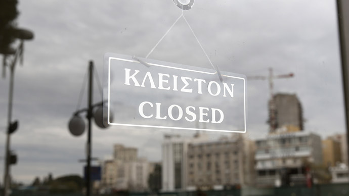 People are reflected at a glass door of a closed branch of Bank of Cyprus in Nicosia March 19, 2013. (Reuters)