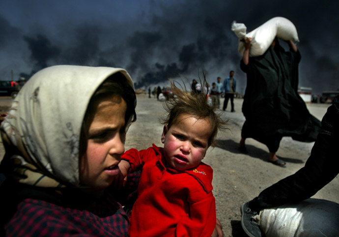 An Iraqi girl holds her sister as she waits for her mother (R) to bring over food bought in Basra, March 29, 2003. (Reuters/Jerry Lampen)