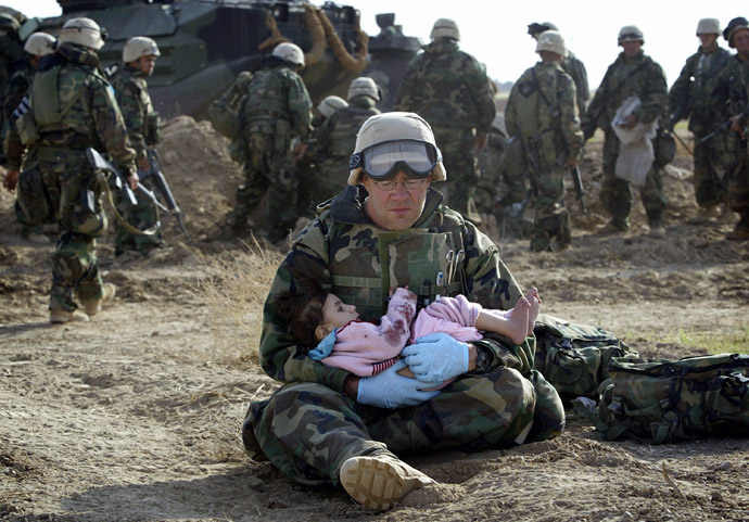 U.S. Navy Hospital Corpsman HM1 Richard Barnett, assigned to the 1st Marine Division, holds an Iraqi child in central Iraq in this March 29, 2003 file photo. (Reuters/Damir Sagolj)