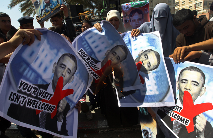 Relatives of prisoners of Palestinians held in Israeli jails burn pictures of US President Barack Obama during a protest against his visit to the region at the Jabalyia refugee camp, in the northern Gaza Strip, on March 20, 2013 (AFP Photo / Mahmud Hams)