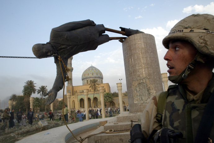 U.S. Marine Corp Assaultman Kirk Dalrymple watches as a statue of Iraq's President Saddam Hussein falls in central Baghdad April 9, 2003 (Reuters / Goran Tomasevic)