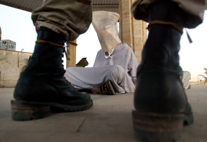 A U.S.soldier of the 1st Battalion (22nd regiment) of the fourth Division of the U.S. army stands guard next to detained Iraqis caught during a raid in Tikrit, September 10, 2003 (Reuters / Arko Datta)
