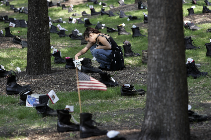 Michelle Rivas of Chicago looks at a set of combat boots placed in Grant Park 24 May, 2007 in Chicago, Illinois as part of the Eyes Wide Open: An Exhibition on the Human Cost of the Iraq War (AFP Photo)