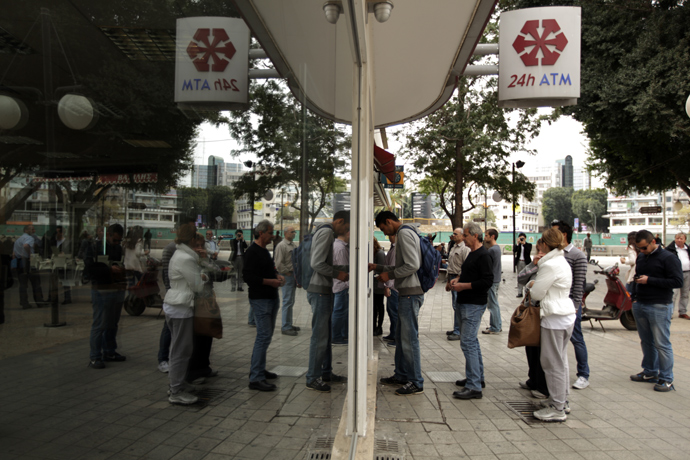 Cypriots and foreigners wait in line to withdraw money from an ATM of a Laiki (Popular) Bank branch in the old city of the capital, Nicosia, on March 21, 2013 (AFP Photo / Patrick Baz)