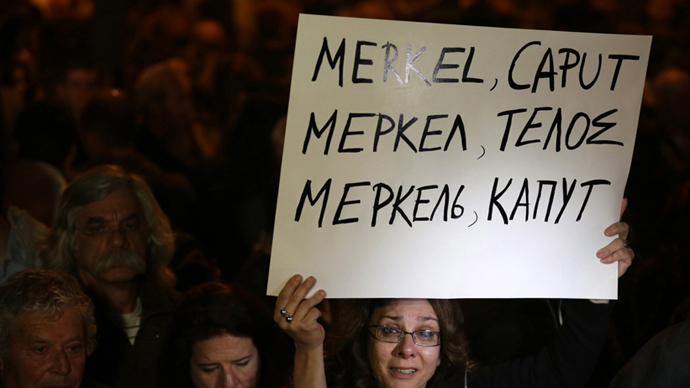 "A Cypriot empoyee of the Laiki (Popular) Bank cries as she holds a placard reading in Greek, Russian and English ""Merkel Caput"" during a protest outside the Parliament on March 21, 2013 in Nicosia (AFP Photo / Patrick Baz)"