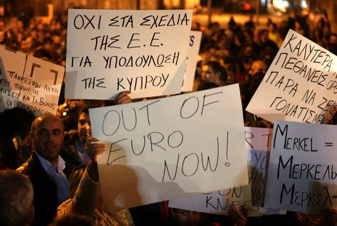 Cypriots hold placards during a protest outside the Parliament on March 21, 2013 in Nicosia (AFP Photo / Patrick Baz)