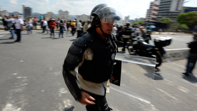 A riot police officer runs in downtown Caracas on March 21, 2013 during a demonstration of opposition students demanding to the National Electoral Council (CNE) transparency during the presidential elections next February 14 (AFP Photo / Juan Barreto)
