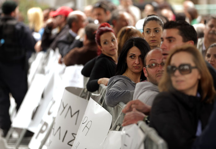 Employees of Cyprus Laiki (Popular) Bank gather as they protest outside the parliament in Nicosia.(AFP Photo / Patrick Baz)