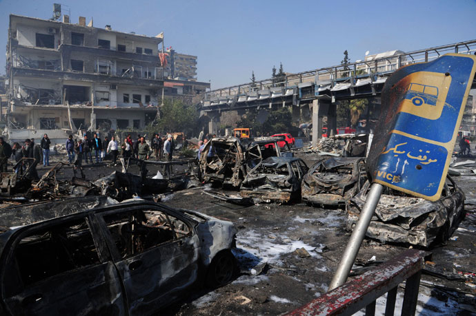People walk near debris and damaged vehicles after an explosion at central Damascus February 21, 2013.(Reuters / Sana)