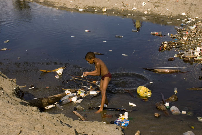 A boy plays in a pool of polluted water near the sea on a beach next to the main port in Haina.(Reuters / Eduardo Munoz)