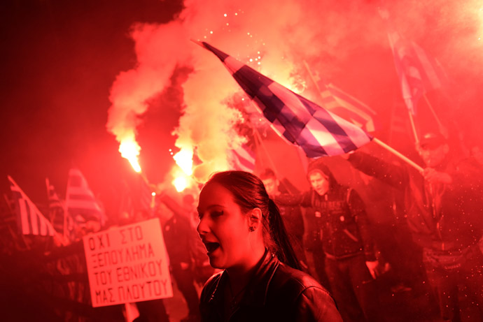 Some of about 1,000 members of the ultra-nationalist Golden Dawn party hold flares while chanting the Greek national anthem on March 22, 2013 outside the German Embassy in Athens against the EU austerity plans for Cyprus. (AFP Photo/Aris Messinis)