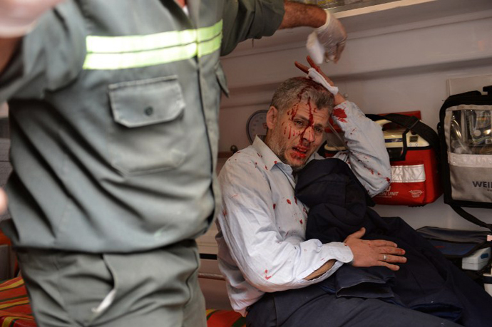 An Egyptian man is treated in an ambulance after being injured during clashes part of a protest of members of Egyptian Muslim brotherhood in front the party's headquarters in Cairo on March 22, 2013. (AFP Photo / Haled Desouki)