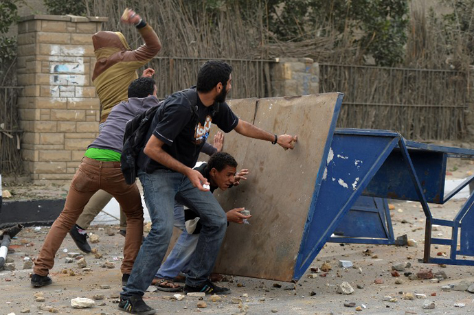 Egyptian protesters take cover during clashes with members of the Muslim Brotherhood near the movements' headquarters in Cairo on March 22, 2013. (AFP Photo / Haled Desouki)