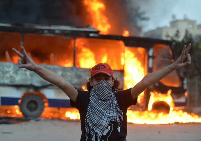 An Egyptian protester flashes the sign of victory in front of a bus belonging to the Egyptian Muslim Brotherhood on fire during clashes near the movements' headquarters in Cairo on March 22, 2013. (AFP Photo / Haled Desouki)