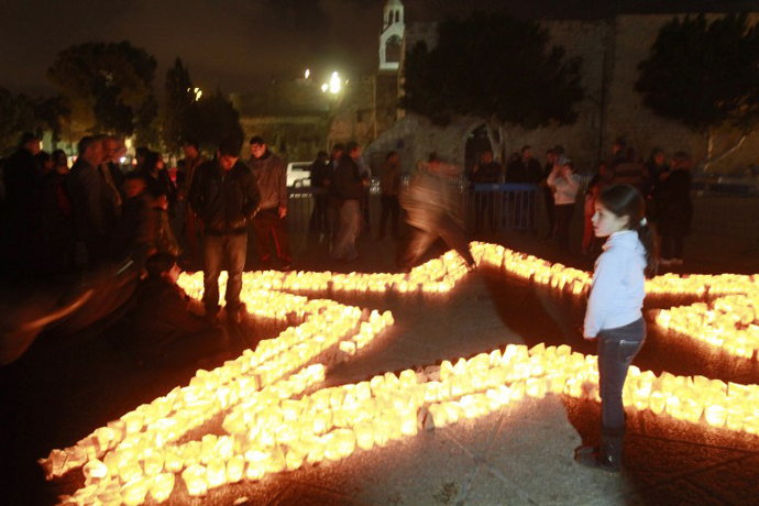A child looks on as members of Palestine Wildlife Society outline the star of Bethlehem with candles at the Manager Square in front of the Church of the Nativity in the West Bank town of Bethlehem on March 23, 2013, to mark the Earth Hour for the first time in Palestine. (AFP Photo / Musa al-Shaer)