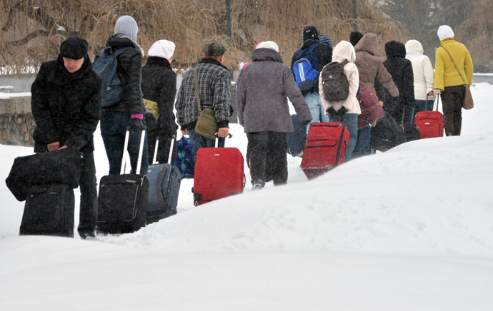 Tourists carry their luggage during a snow storm in the Ukraine capital Kiev on March 23, 2013. (AFP Photo / Sergei Supinsky)