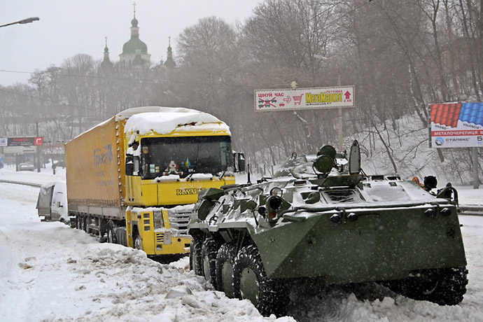 An armored personnel carrier tows a vehicle on a road covered with snow in Kiev on March 23, 2013. (AFP Photo)