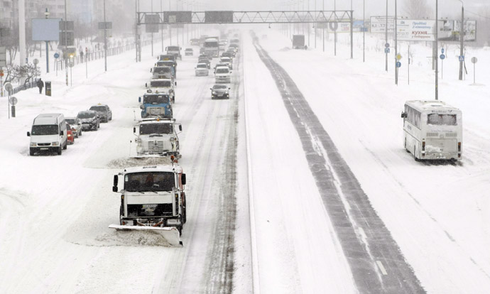 A convoy of snow clearing vehicles work along a main road after a heavy snowfall in Kiev, March 23, 2013. (Reuters)