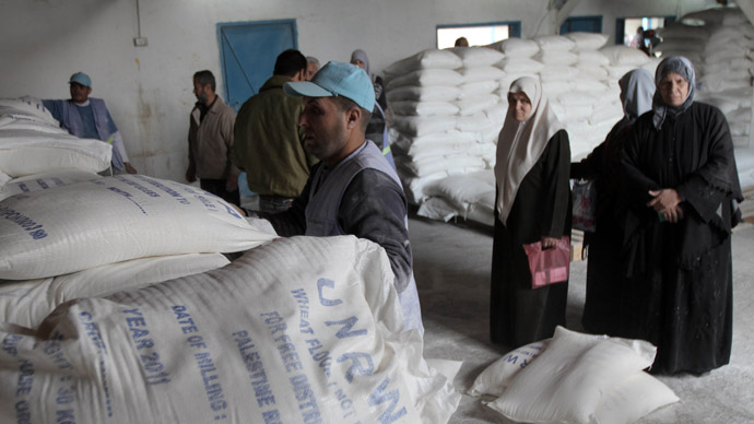Palestinians wait to receive their monthly food aid at a UN distribution center in the Shati refugee camp, in Gaza City, on January 17, 2012. (AFP Photo/Said Khatib)